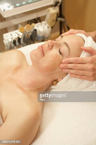 Woman receiving massage in spa, eyes closed, elevated view
