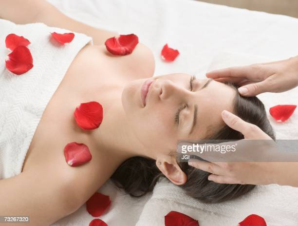 Woman receiving massage with flower petals on table