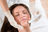 Young Woman Receiving Microdermabrasion Therapy In Beauty Clinic