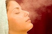 Young woman receiving steam bath, eyes closed, close-up