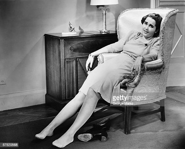Woman reclining in armchair, exhausted, (B&W)