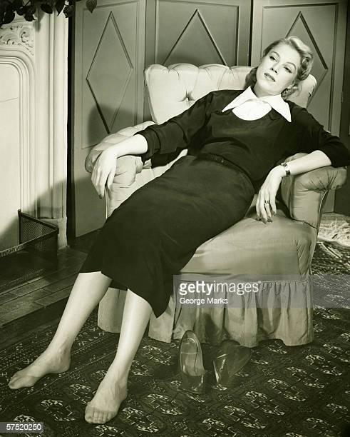 Woman reclining in armchair, (B&W)