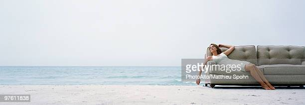 Woman reclining on couch on beach at water's edge
