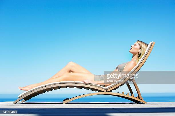 Woman reclining on folding chair in bikini outdoors
