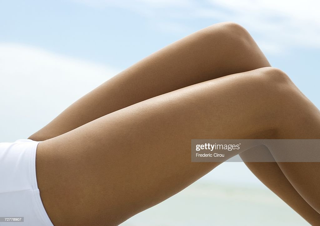 Woman reclining with knees up, close-up of bare legs
