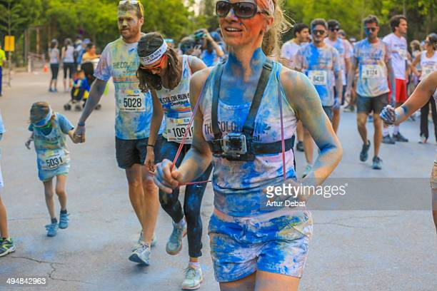 Woman recording in first person with GoPro in the Color Run by Desigual Blue color powder Barcelona Catalonia May 18th 2014 Wearable technology
