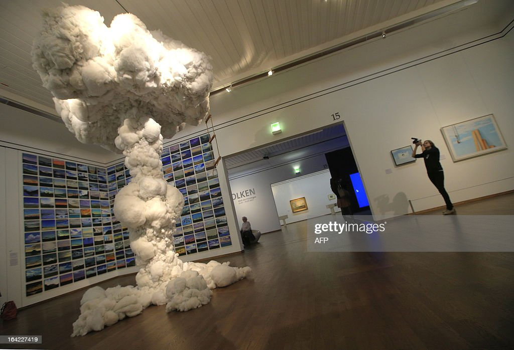 A woman records next to an artwork by Australian artist Dietrich Wegner, titled 'Playhouse' and dated 2008-2012, as part of the 'Clouds' (Wolken) exhibition at the Leopold Museum in Vienna, on March 21, 2013. The exhibition will run until July 1, 2013.
