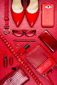 Red woman accessories, jewelry, clothing, gadget, cosmetic and other objects on leather background, fashion industry, modern female concept