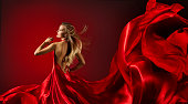 Woman in Red Dress Dancing, Fashion Model with Flying Cloth Fabric over red background