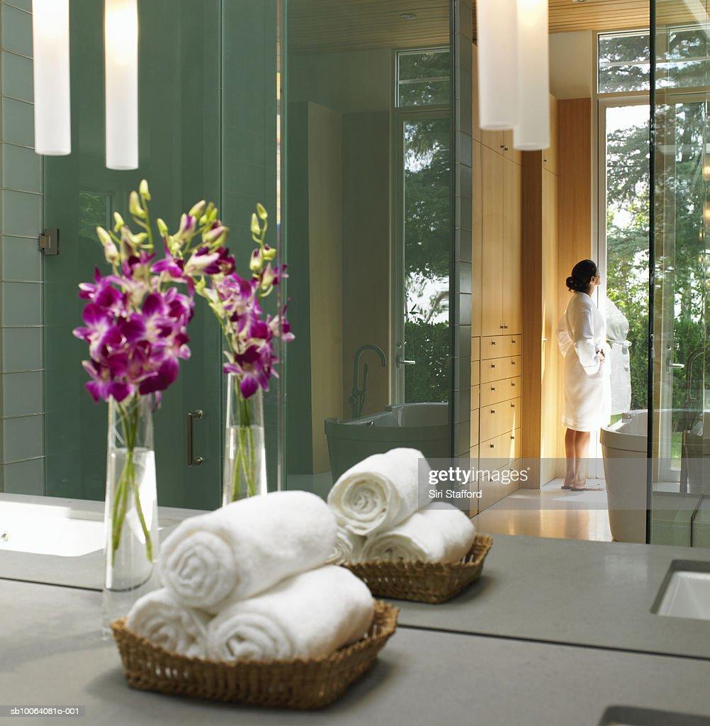 Woman reflected in bathroom mirror standing near doorway in white robe : Stock Photo