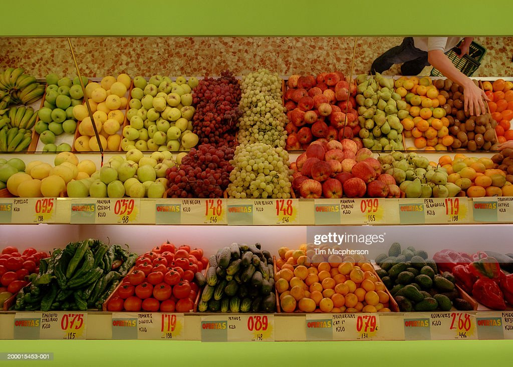 Woman reflected in mirror of produce section in supermarket : Stock Photo