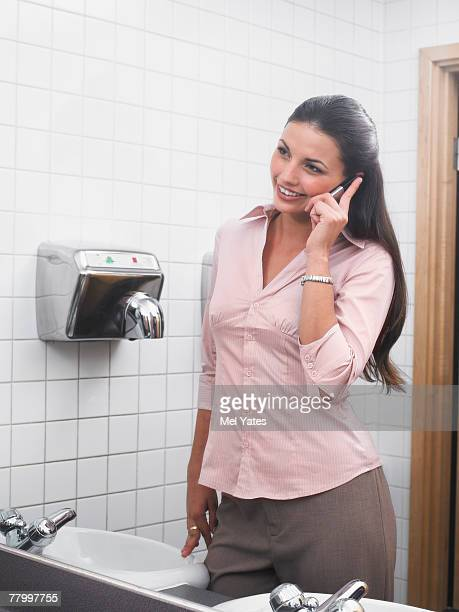 Woman reflected in office washroom mirror using mobile phone