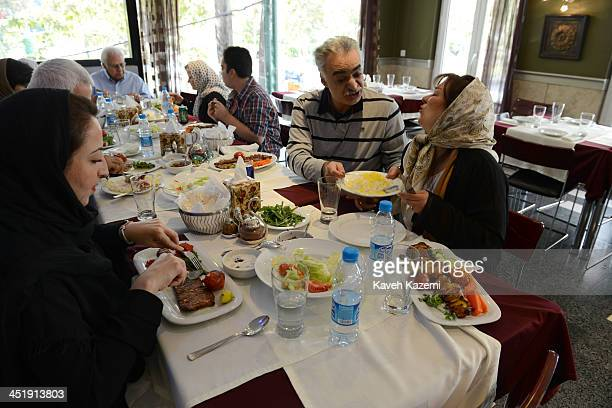 A woman refuses having rice with her food while sat with the family eating the traditional Iranian dish CheloKebab in Yas restaurant on October 10...