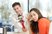 Disgusted woman rejecting a geek boy offering flowers in a blind date in a coffee shop interior