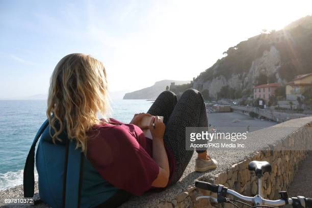 Woman relaxes above sea with bike, writes in journal