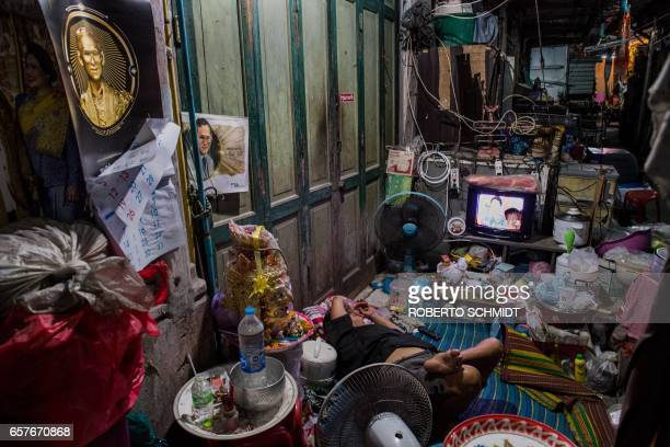 TOPSHOT A woman relaxes as she watches a tv program near cubicles where people live on the river front in Bangkok on March 25 2017 / AFP PHOTO /...