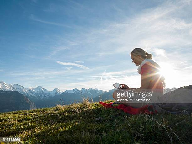 Woman relaxes in alpine meadow,uses digital tablet