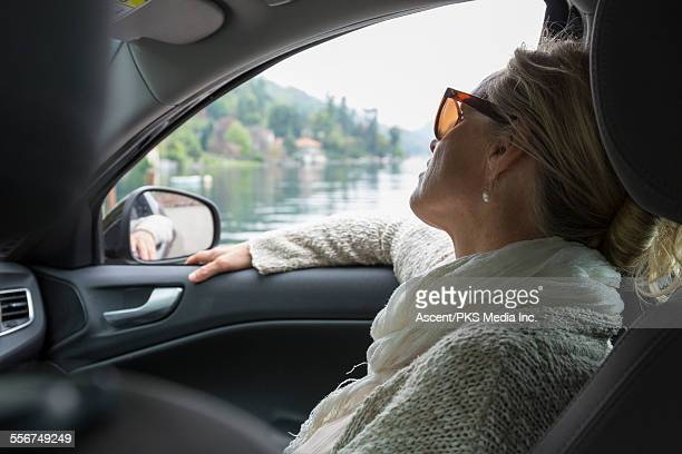 Woman relaxes in car, looks out across lake