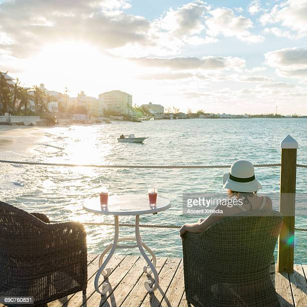 Woman relaxes in chair with drink, looks to sea