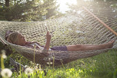 Woman relaxes in hammock, uses digital tablet