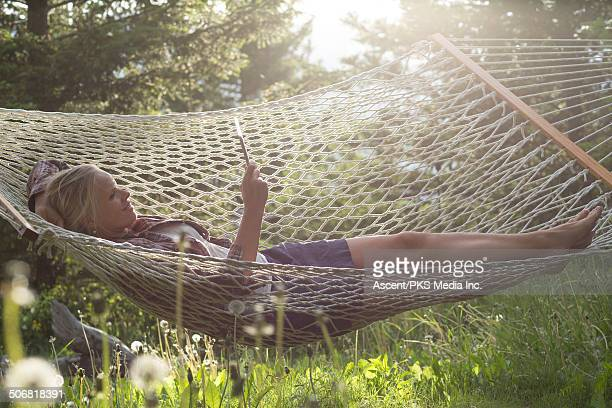 Woman relaxes in hammock, uses digital tablet