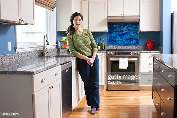A woman relaxes in her kitchen and leans against the kitchen counter.