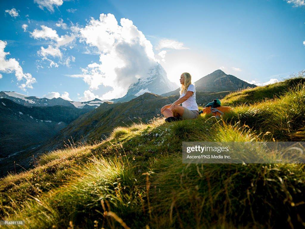 Woman relaxes in mountain meadow below Matterhorn