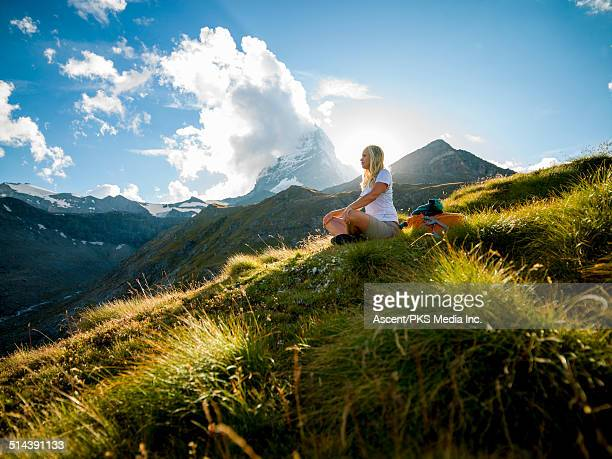Woman relaxes in mountain meadow below Matterhorn
