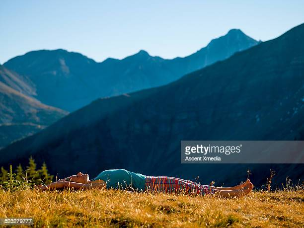 Woman relaxes in mountain meadow, in solitude