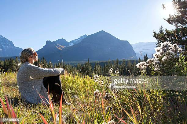 Woman relaxes in mountain meadow, smiling