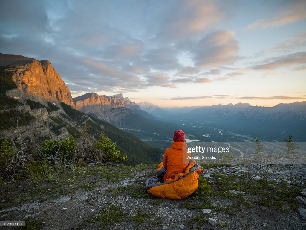 Woman relaxes in sleeping bag, high mountain perch