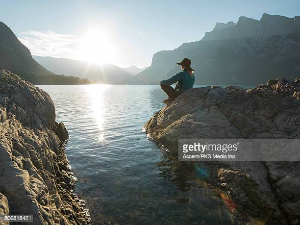 Woman relaxes in yoga pose at lake edge, sunrise