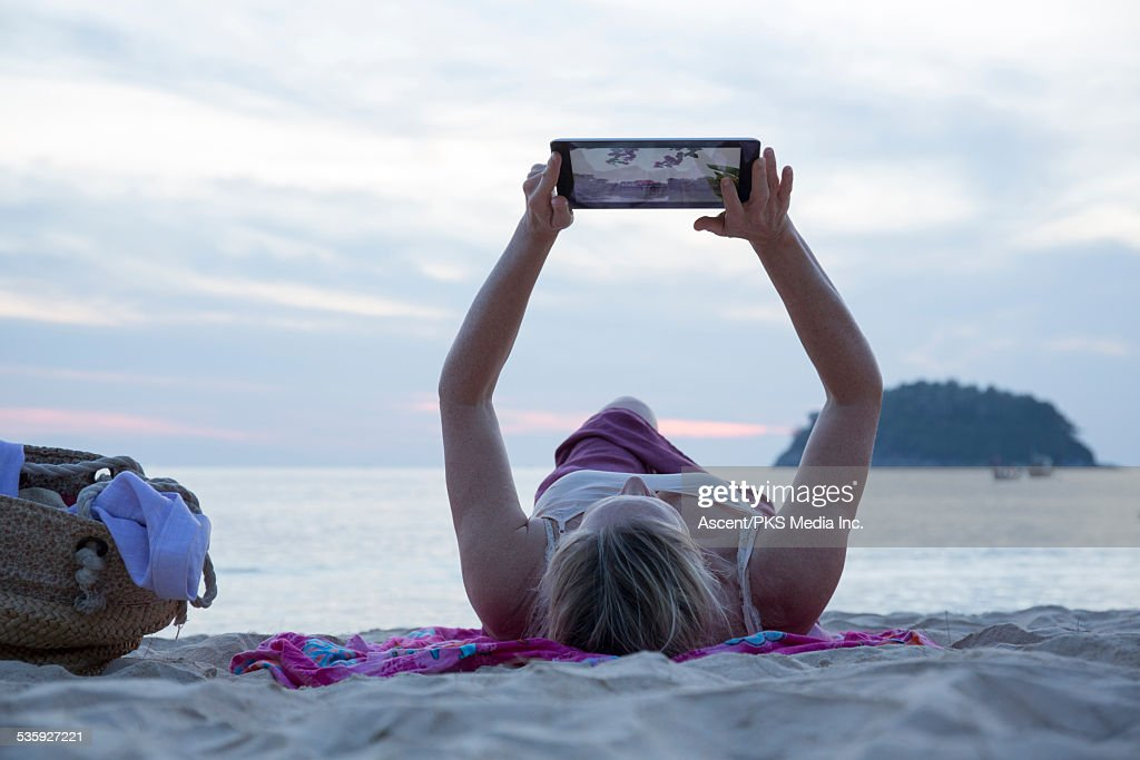 Woman relaxes on beach, holds tablet overhead : Stock Photo