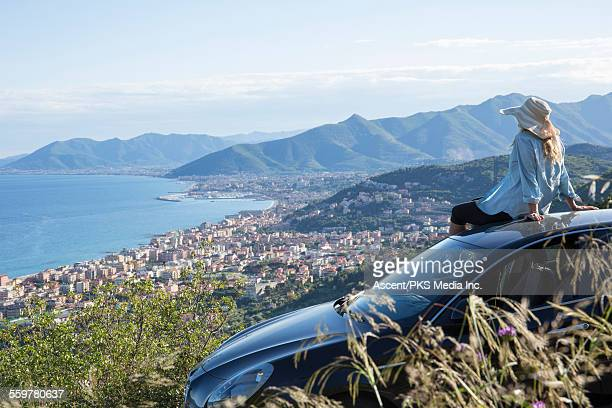 Woman relaxes on car,looks out across town and sea
