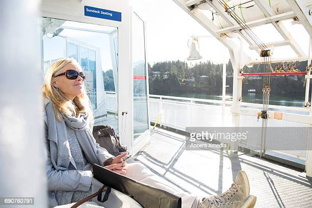 Woman relaxes on ferry boat, sending text