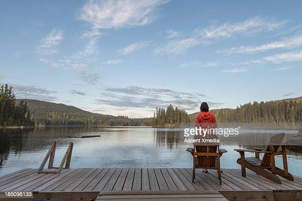 Woman relaxes on lake dock, looks across lake