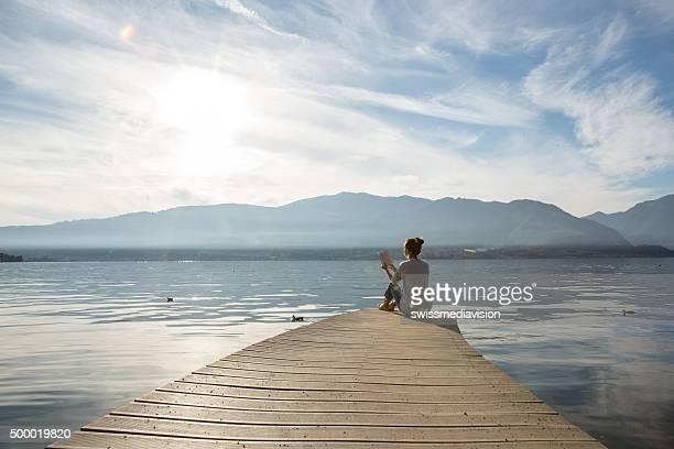 Mulher relaxa no lago cais, lê um livro de endereços