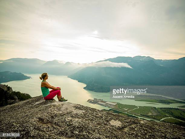 Woman relaxes on mtn summit, looks out