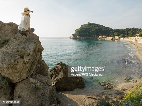 Woman relaxes on rock cliff above cove, sea