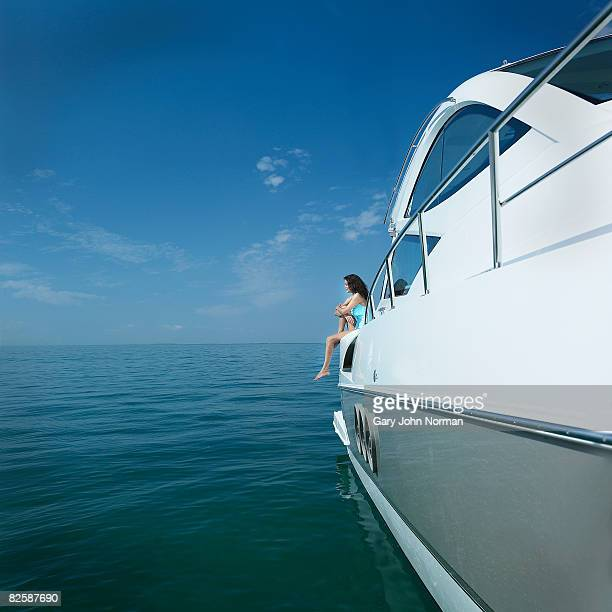 Woman relaxes on stern of power boat