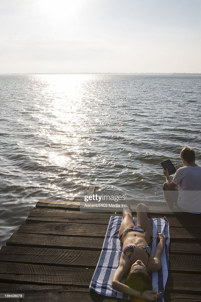 Woman relaxes on wharf, man uses digital tablet : Stock Photo