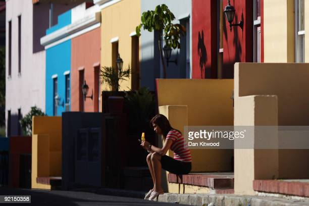 A woman relaxes outside a house in the BoKaap area of Cape Town on October 20 2009 in Cape Town South Africa The BoKaap area is a predominantly...