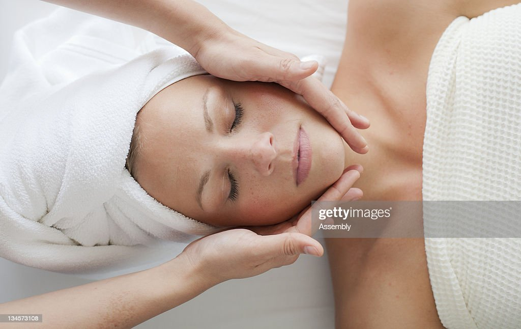 A woman relaxes while getting a facial. : Stock Photo