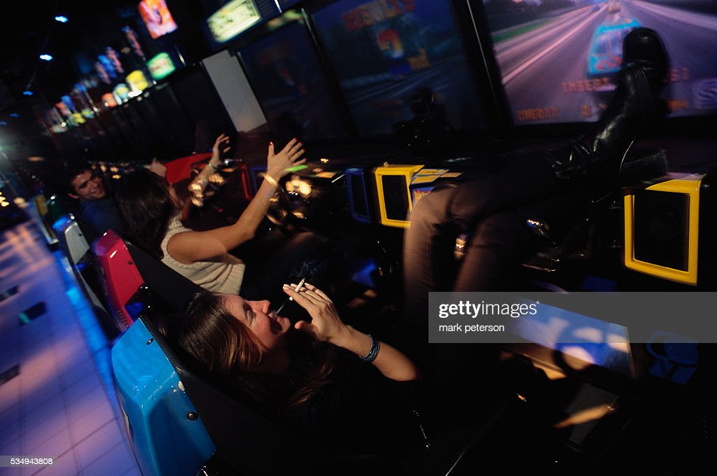 A woman relaxes with her friends at Bar Code a New York video arcade bar where DJs play music at night