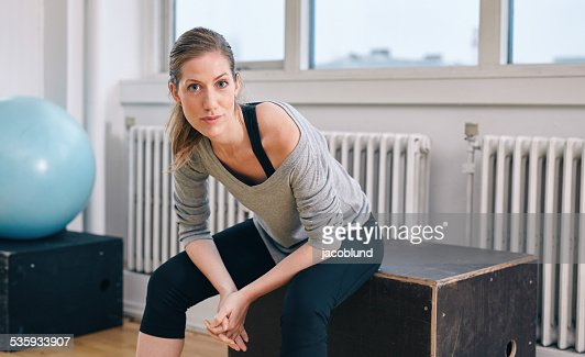 Woman relaxing after workout at gym : Stock Photo
