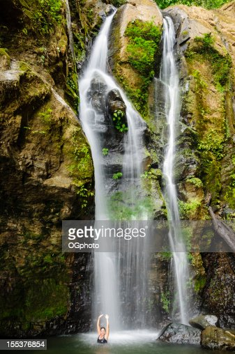 A woman relaxing and bathing under a waterfall : Stock Photo