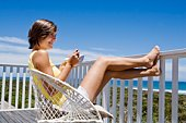 Woman relaxing and eating on balcony