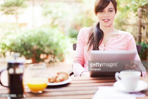 Femme de détente et de travail sur sa terrasse.