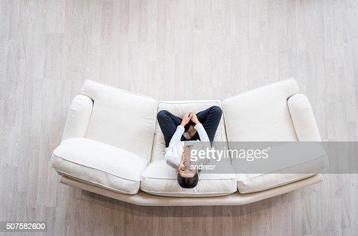 frau entspannen auf dem sofa zu hause stock foto getty. Black Bedroom Furniture Sets. Home Design Ideas