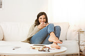 Happy woman sitting on couch holding a cup of tea in living room. Portrait of a young woman drinking a cup of coffee while relaxing on sofa at home. Smiling girl with woolen jacket drinking hot coffee